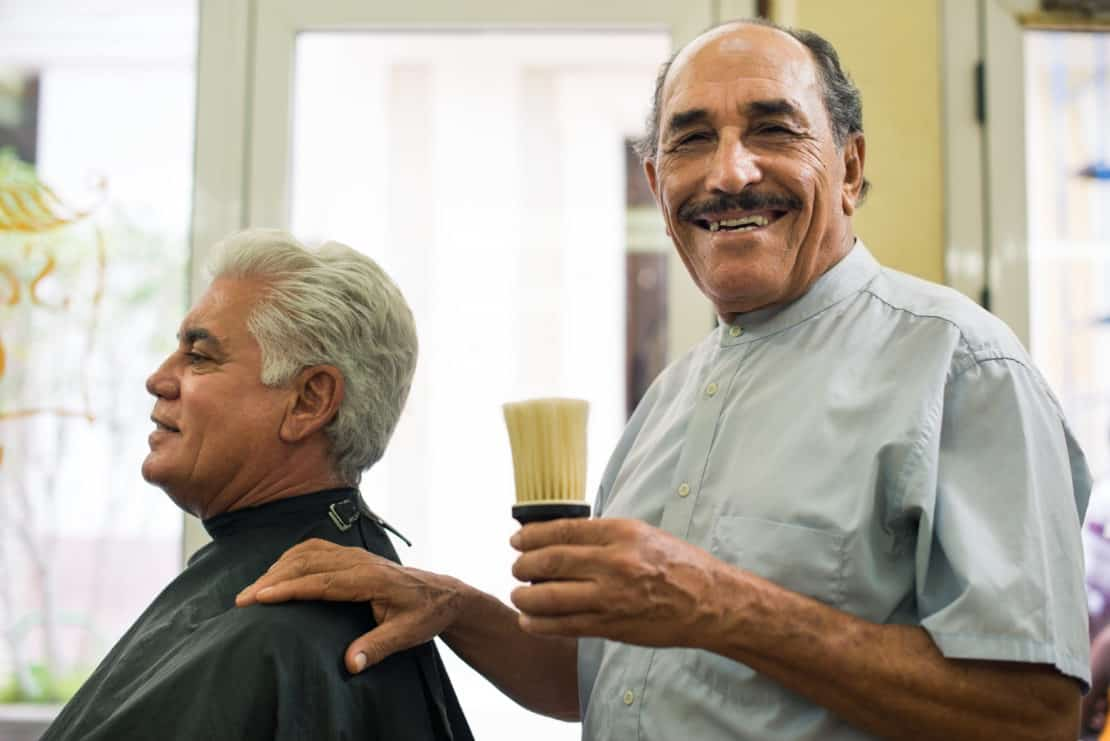 Portrait of senior man working as barber offering great customer service